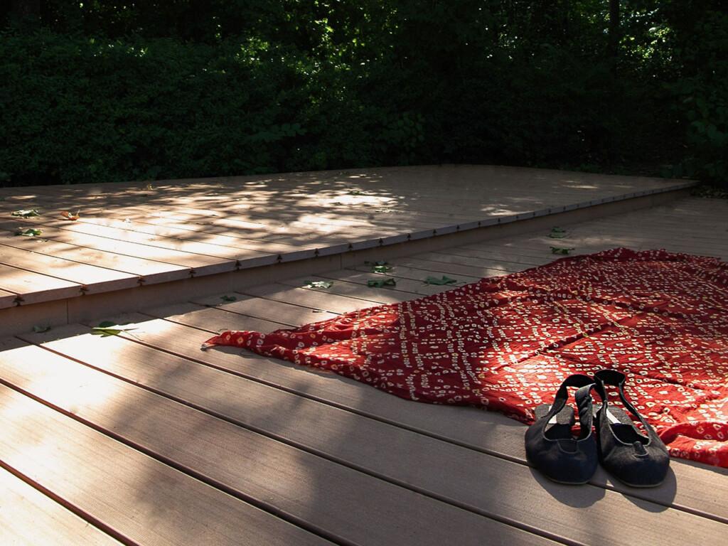 Liegefläche im Schwimmbad mit hellbraunen Barfußdielen und mit ausgebreitetem Handtuch und Schuhen