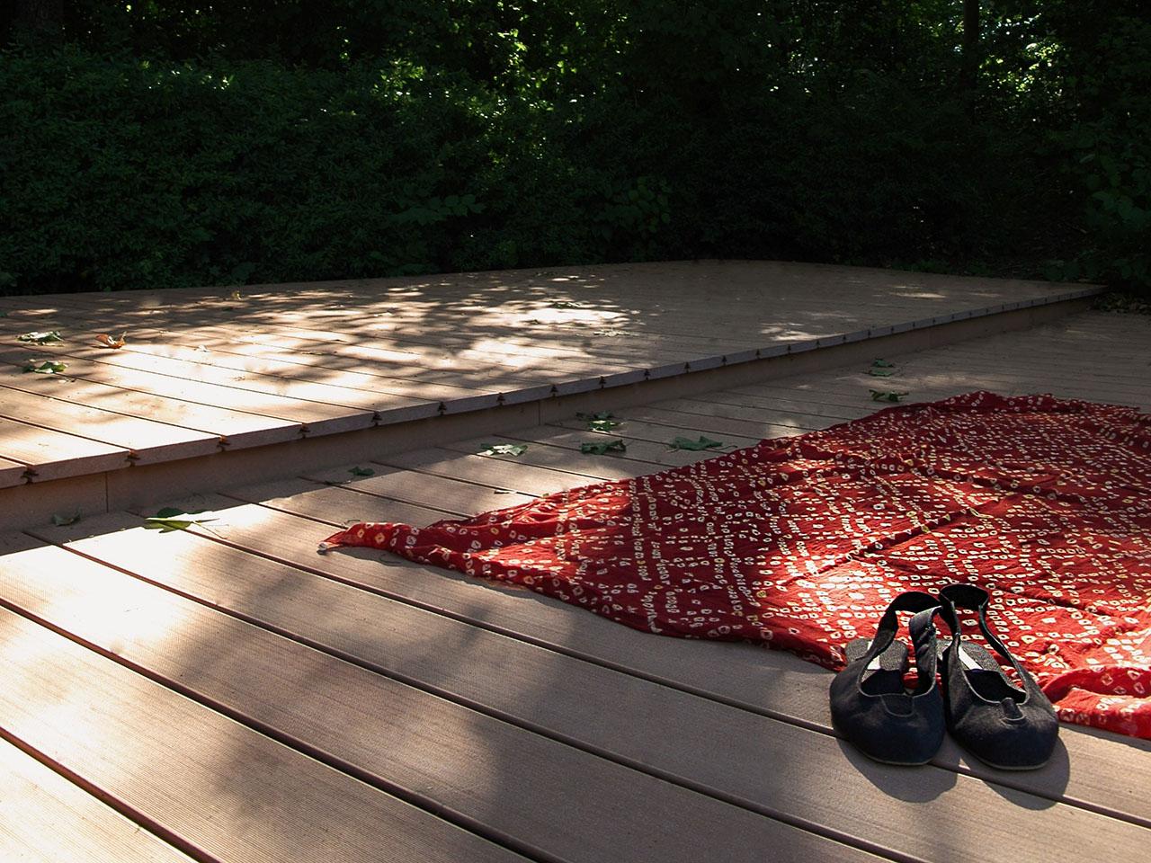 Liegefläche im Schwimmbad mit Barfußdielen aus WPC und rotem Schwimmbadtuch darauf