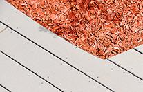 terrassendielen mydeck aus wpc mit roten rindenmulch am terrassenrand