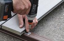Verlegung von WPC Terrassendielen, Nahaufnahme bei der Verschraubung von Clip und Unterkonstruktion