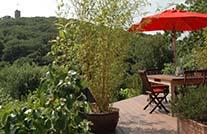 Terrasse im Grünen mit schokobraunen Terrassendielen und rotem Sonnenschirm