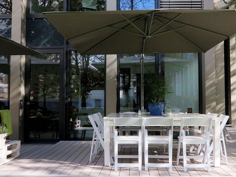 Aussendielen aus grauem WPC auf der Terrasse eines modernen Cafés mit weißen Möbeln