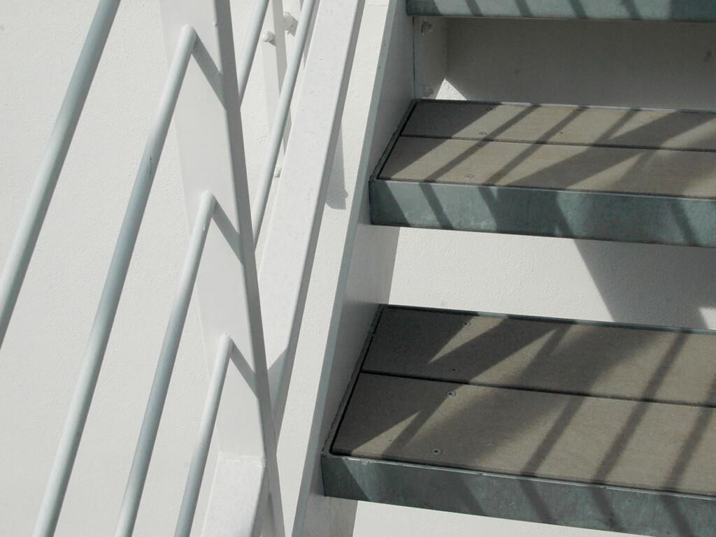 Detail von grauen Treppenstufen mit WPC Terrassendielen auf den Trittflächen verlegt, sowie mit silberner Stahlfassung der Stufen