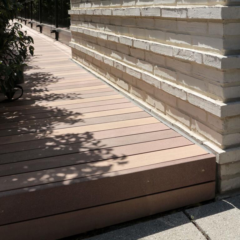 Eine einzelne Stufe mit MYDECK WPC Terrassendielen, die Vorplatz und Terrasse verbindet