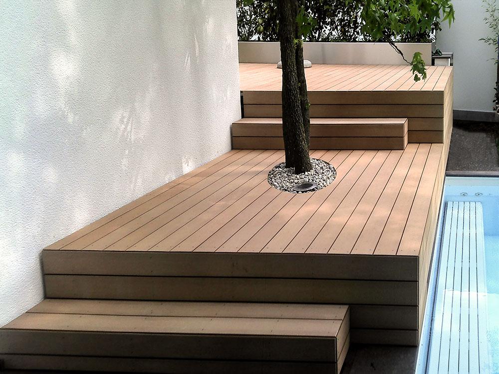 Glatte, hellbraune WPC Terrassendielen massiv auf stufenförmiger Terrasse mit Stufen und Terrassenbelag aus WPC Dielen