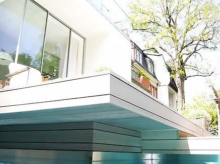 Blick vom Pool auf stufenförmig angeordnete Poolumrandung aus WPC Terrassendielen