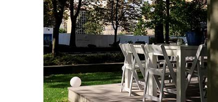 Terrassengestaltung eines Cafés im Grünen mit Baumschatten auf weißer Bestuhlung