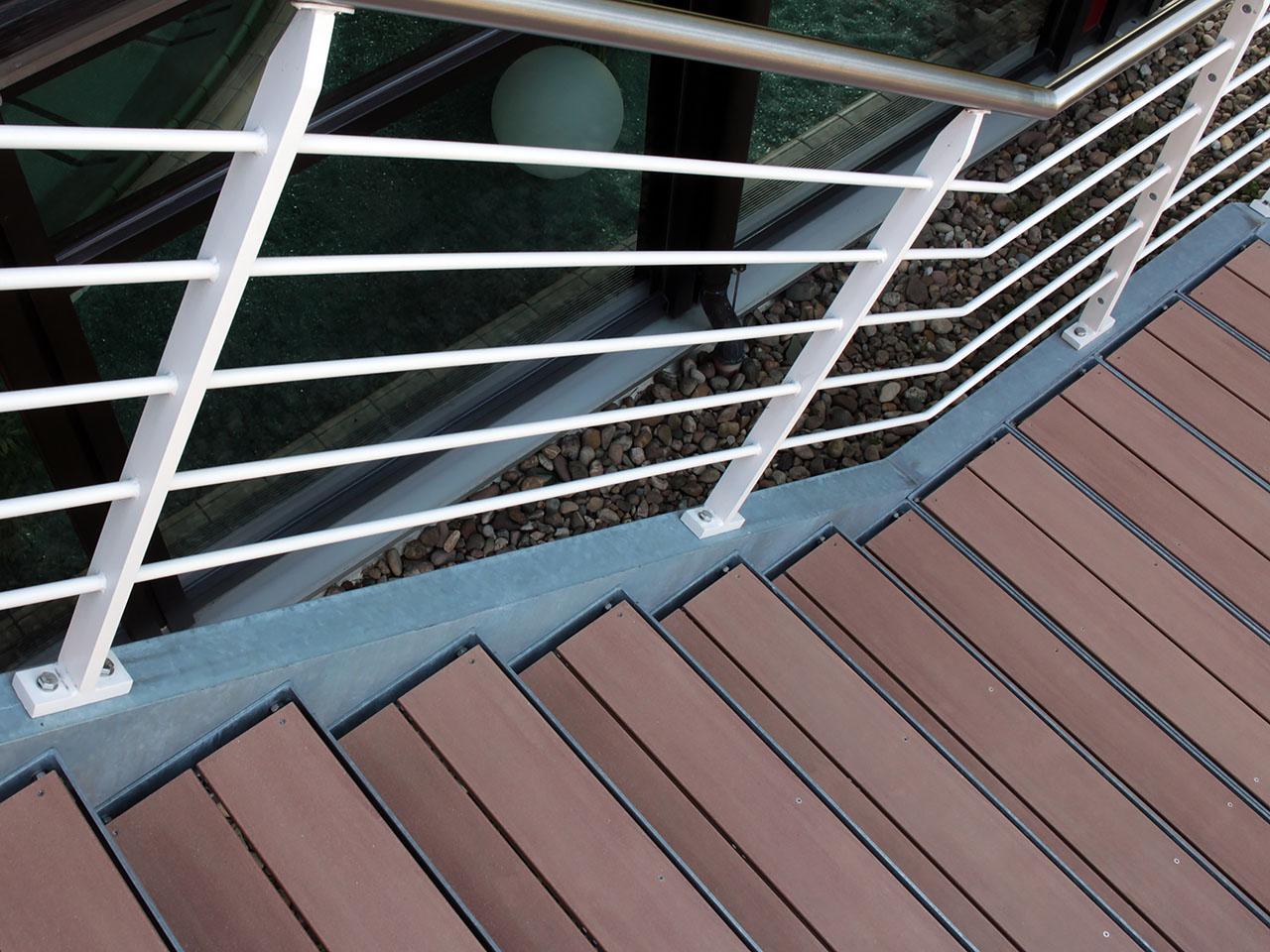 Treppe aus braunen WPC Terrassendielen und einer Einfassung und Geländer aus Stahl