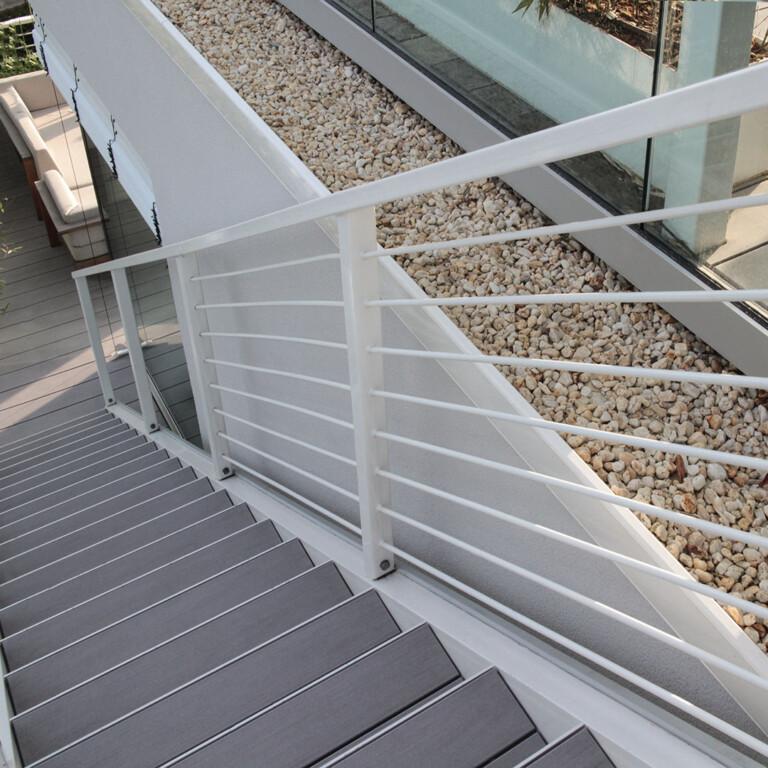 Graue WPC Dielen mit Stahlkonstruktion und Stahlgeländer auf langer Treppe mit vielen Treppenstufen