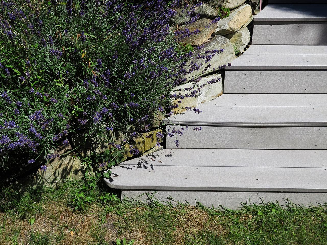 An mediterrane Natursteinmauer grenzende Treppenstufen aus WPC