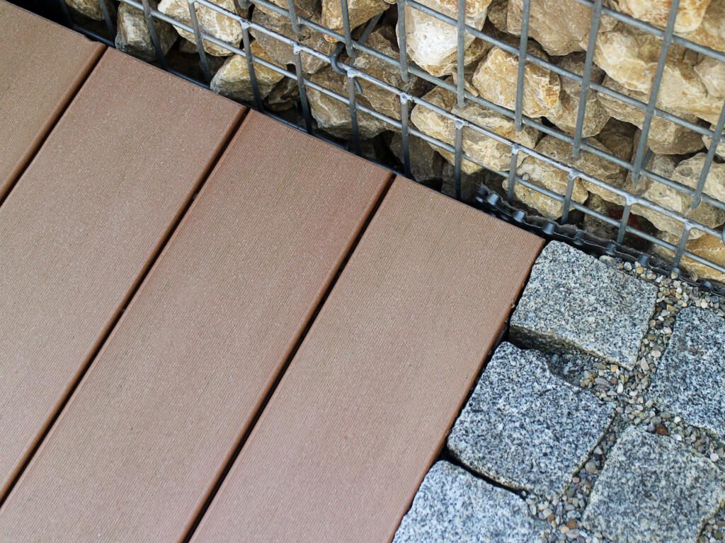 Kombination von zweierlei Steinen und braunen WPC Dielen als Übergang der Terrasse