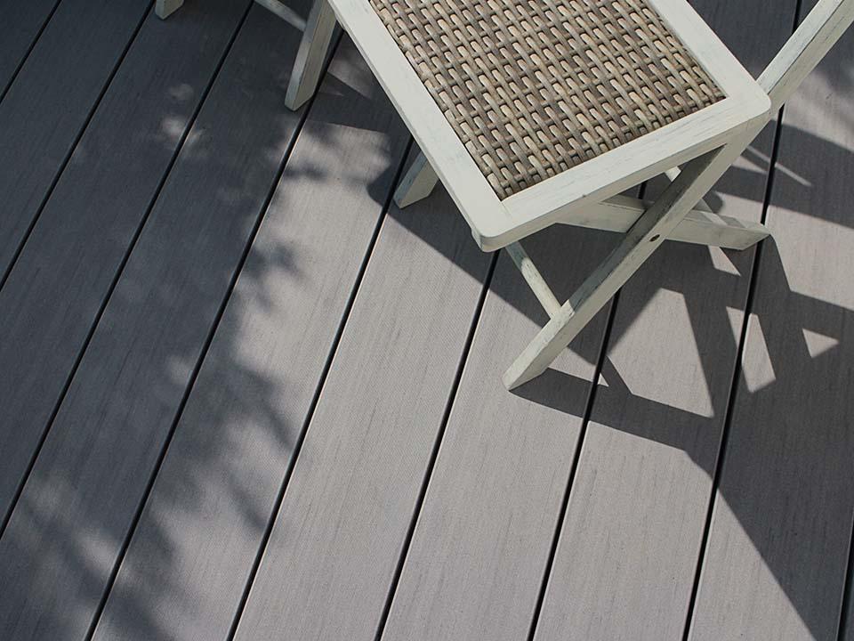 Aufsicht auf die graue Terrassendiele der Pure Kollektion von MYDECK mit Schattenwurf von Stühlen und Pflanzen.