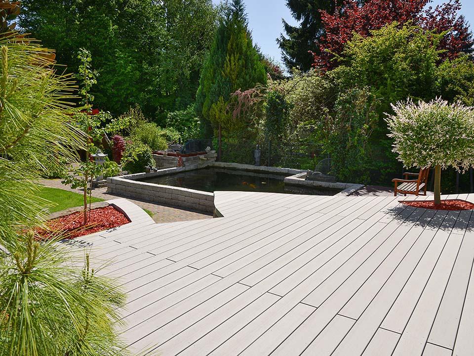 Blick von der leicht geschwungenen Terrasse in den grünen Garten und auf den Fischteich