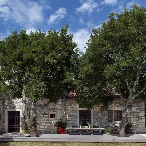 Die Sitzfläche und Terrassenfläche aus grauen WPC Terrassendielen von MYDECK wurde um die 2 Bäume vorm Haus herum gebaut