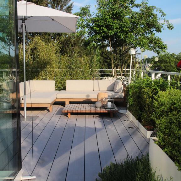 Bildschöne Terrassengestaltung mit integrierten Lichtern in den grauen WPC Dielen und Sitzecke