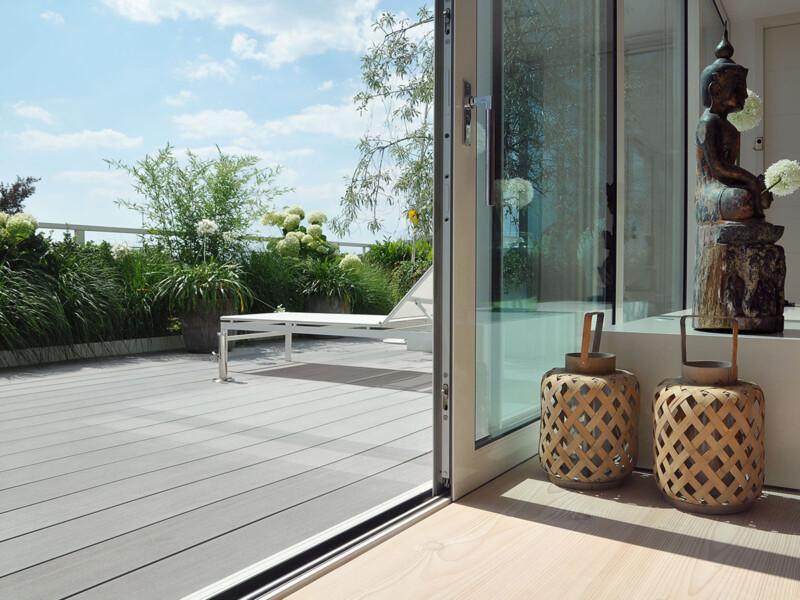 Die moderne Design Terrasse mit den grauen WPC Terrassendielen harmoniert mit dem modernen Interieurdesign