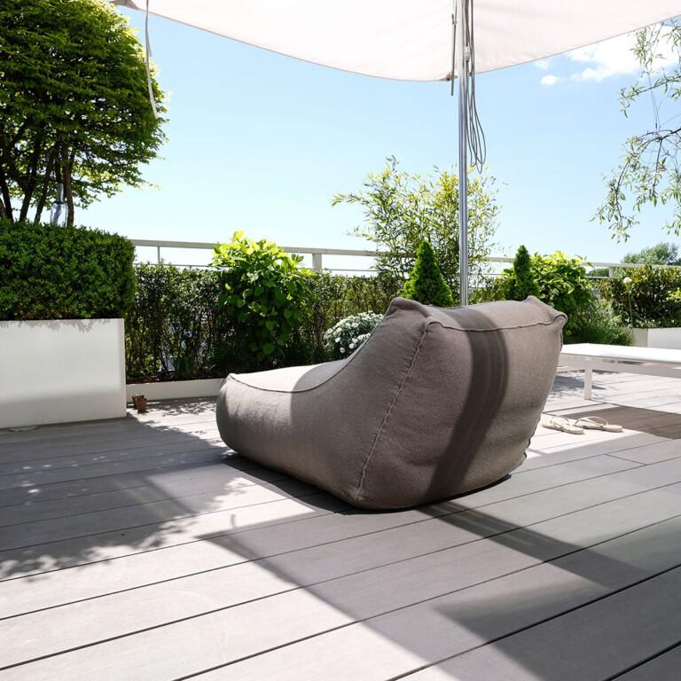 Graue WPC Dielen und eine gemütliche Sitzmöglichkeit mit Blick auf Pflanzen des Dachgartens.