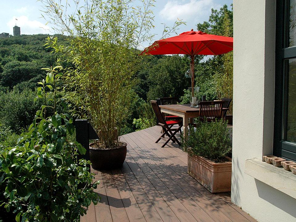 Schöne moderne Terrasse im Landhausstil mit WPC Massivdielen, viel begrünung, Terracotta und einer gemütlichen Sitzecke