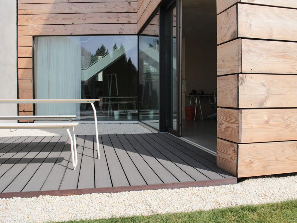 Graue WPC Dielen auf Terrasse umgeben von weißem Kies vor modernem Holzhaus