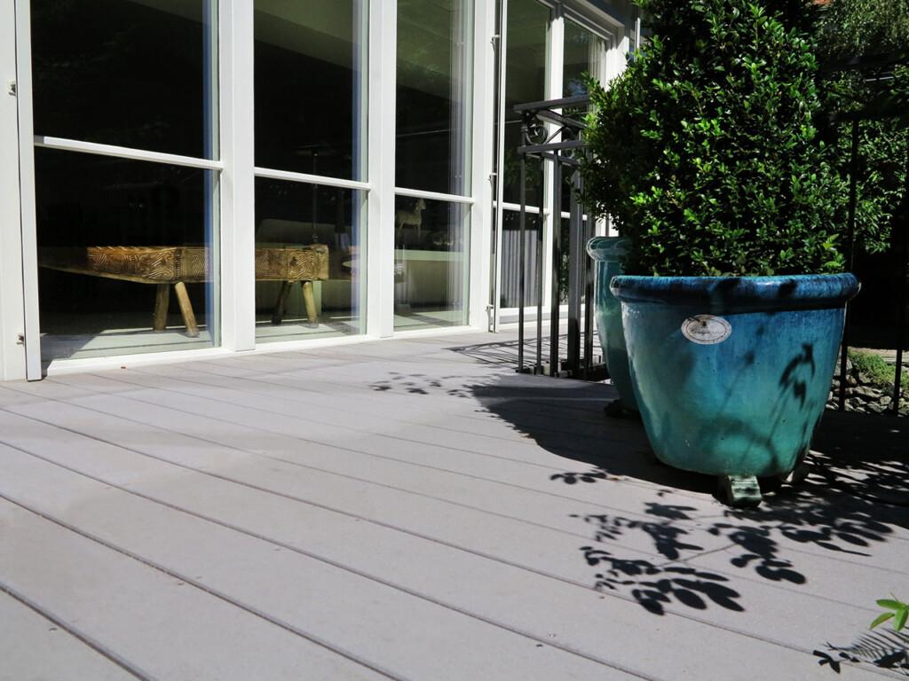 gemütlicher, schöner Landhausstil: Graue WPC Terrassendielen, große farbige Terracottatöpfe, ein geschmiedetes Geländer und Sprossenfenster