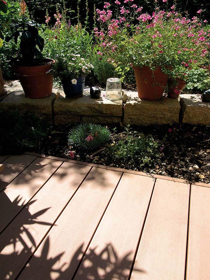 WPC Terrasse die an Blumenbeet und kleines Mäuerchen grenzt, auf dem bepflanzte Blumentöpfe stehen