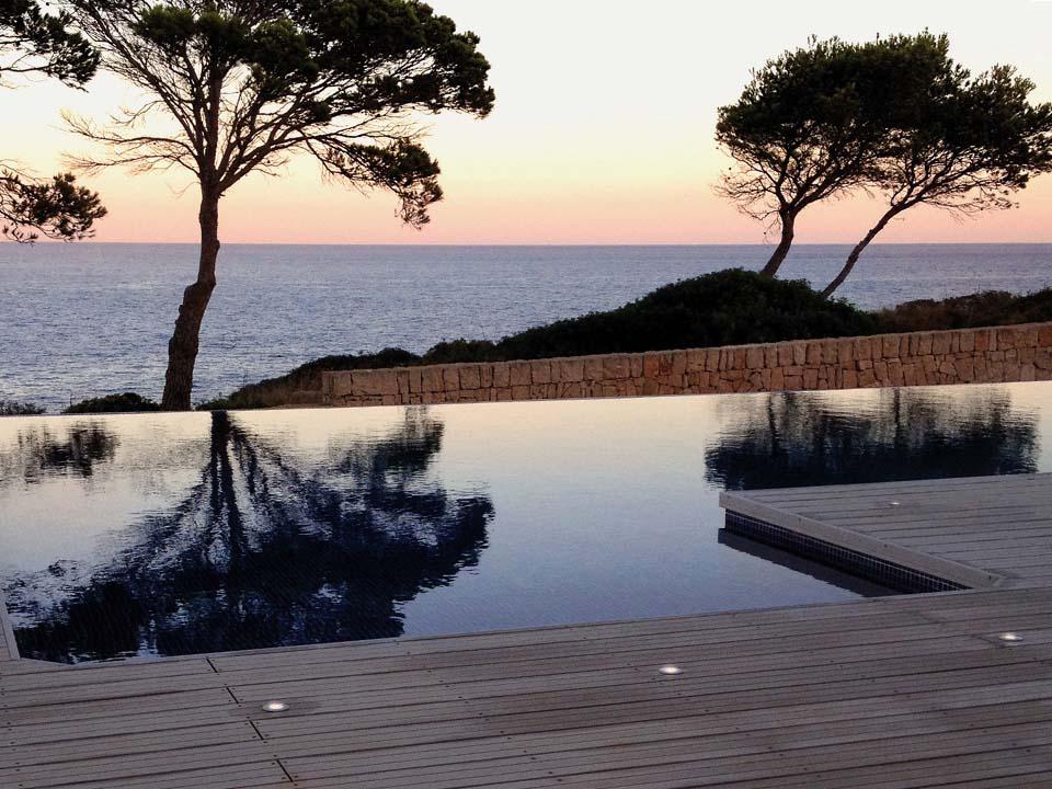 An Pool angrenzende WPC Terrasse mit eingelassenen Lichtern bei Abendstimmung mit Blick aufs Meer.