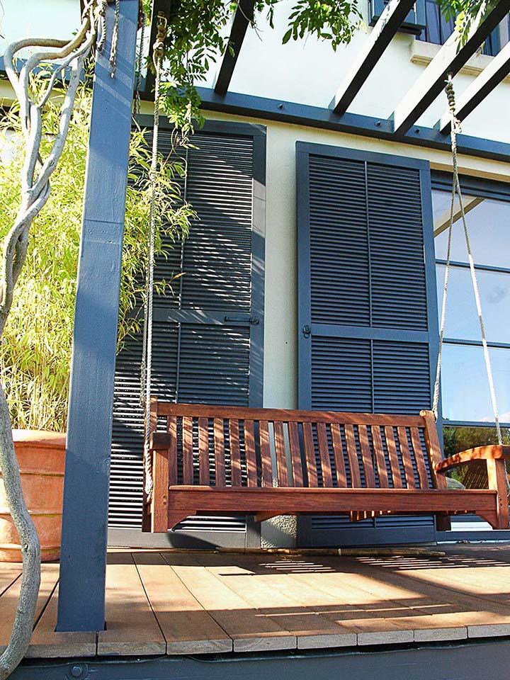 Gemütlicher Sitzplatz unter Pergola mit Pflanzenbewuchs auf WPC Terrasse