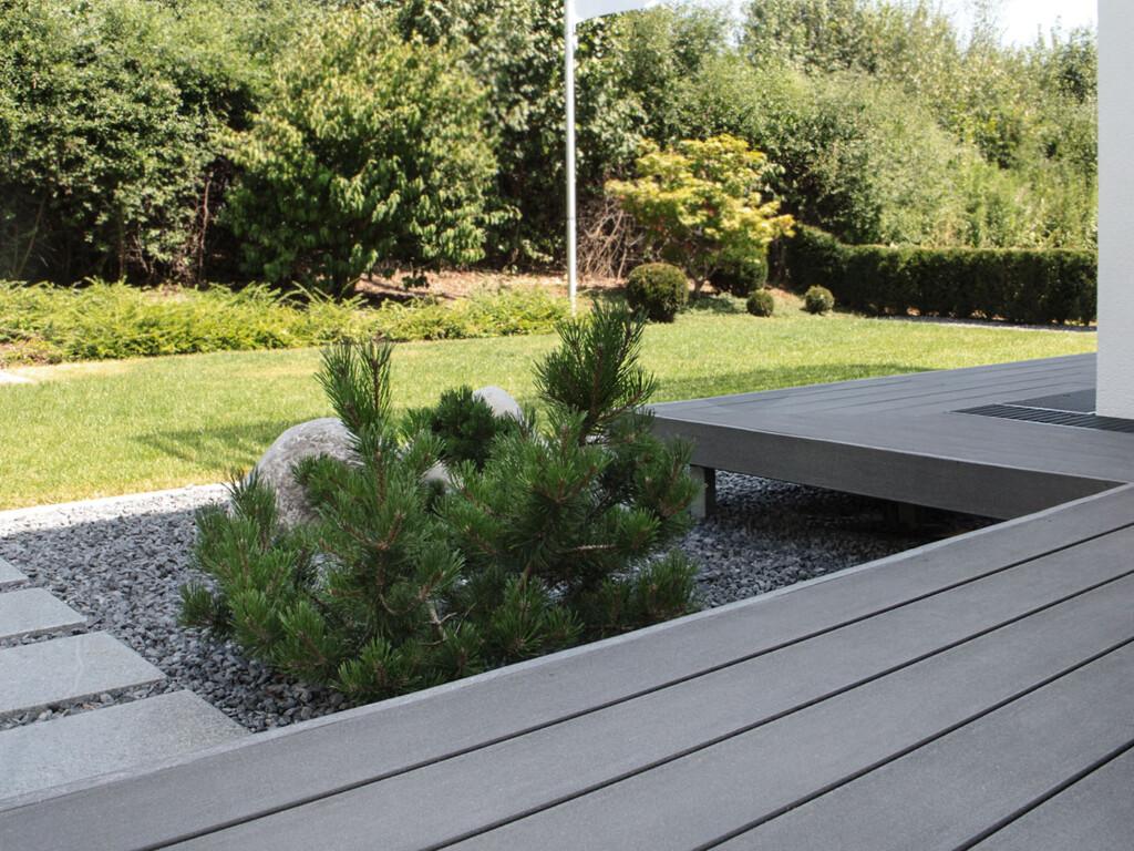 Die dunkelgraue WPC Terrasse scheint zu schweben und gibt Blick in minimalistischen Garten frei