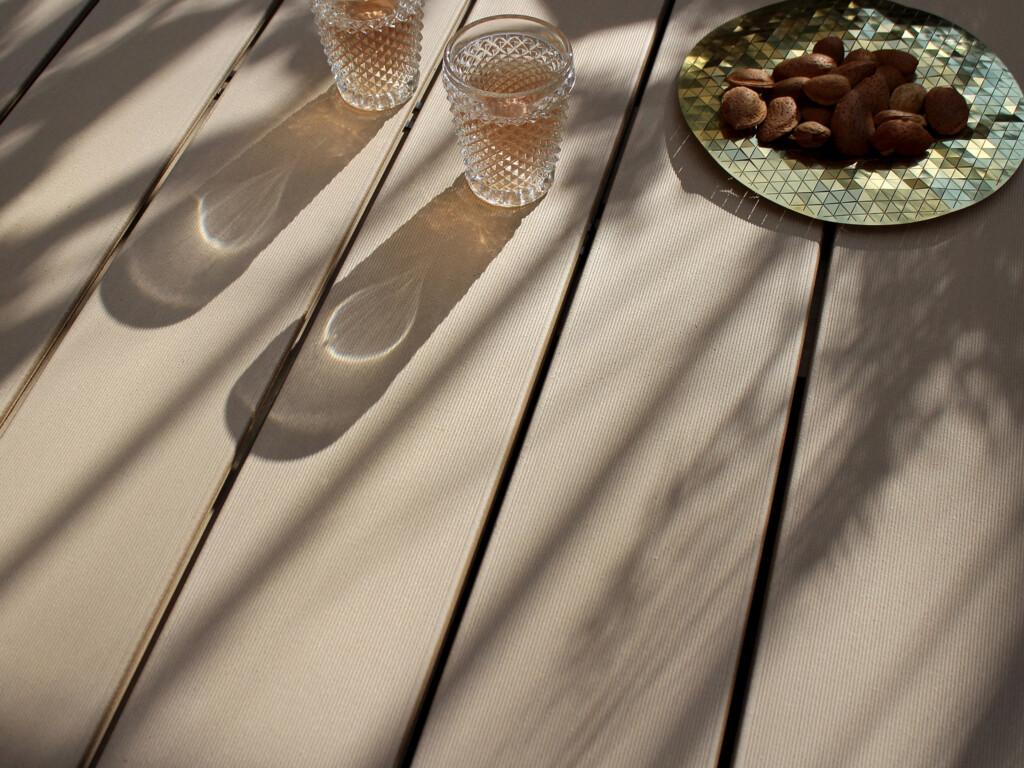 Bildschönes Detailbild von hellbraunen WPC Terrassendielen bei Sonnenschein