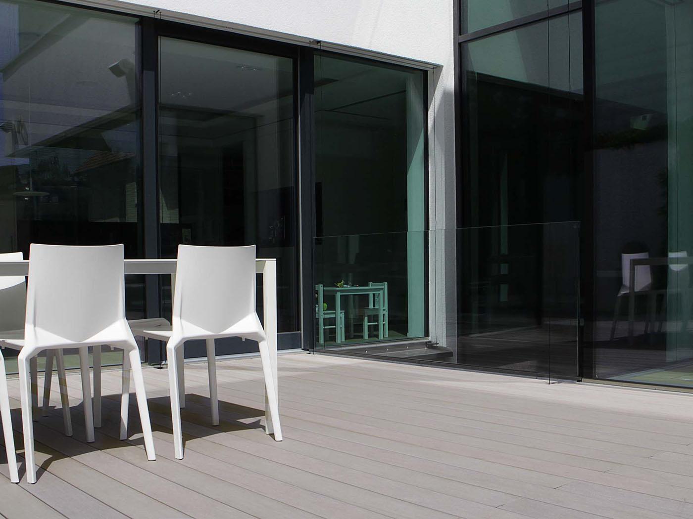 Die steingrauen WPC Terrassendielen fügen sich ideal in das Ambiente der modernen Terrasse mit viel Glas an der Hausfassade ein.