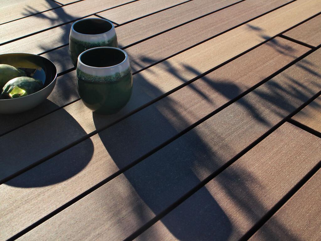 Wood plastic composite Terrassenbelag bei Sonnenschein mit Frühstücksgeschirr