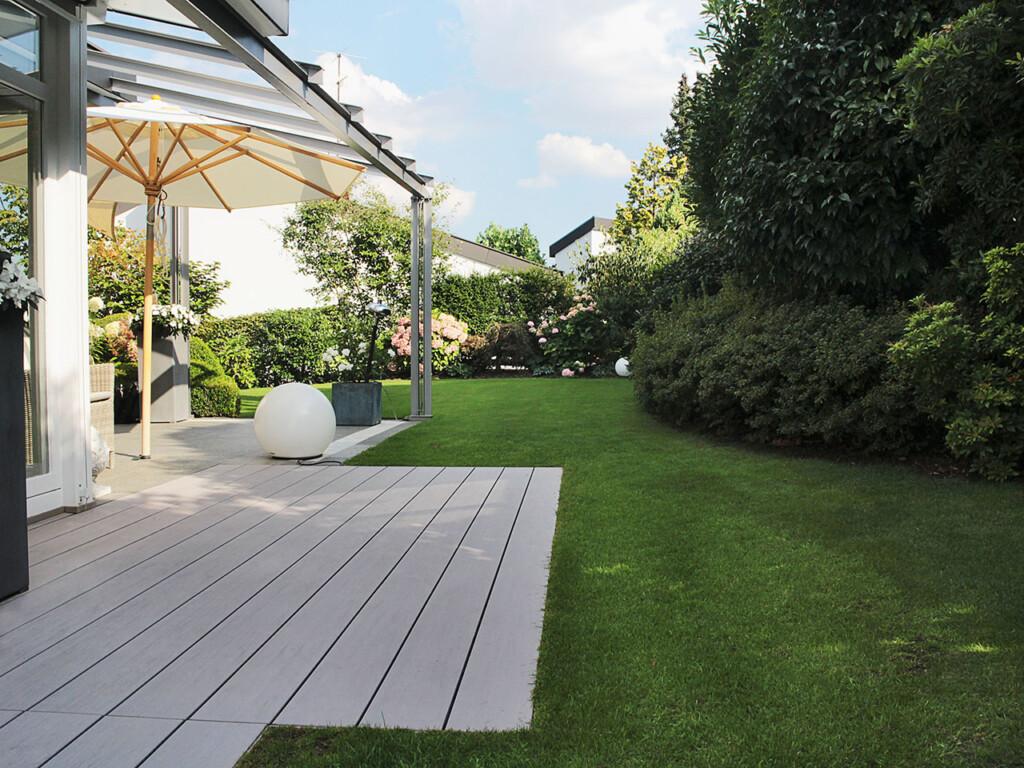 Terrasse mit grauen WPC Dielen (glatt), gepflegter Garten, Sitzplatz mit Sonnenschirm,