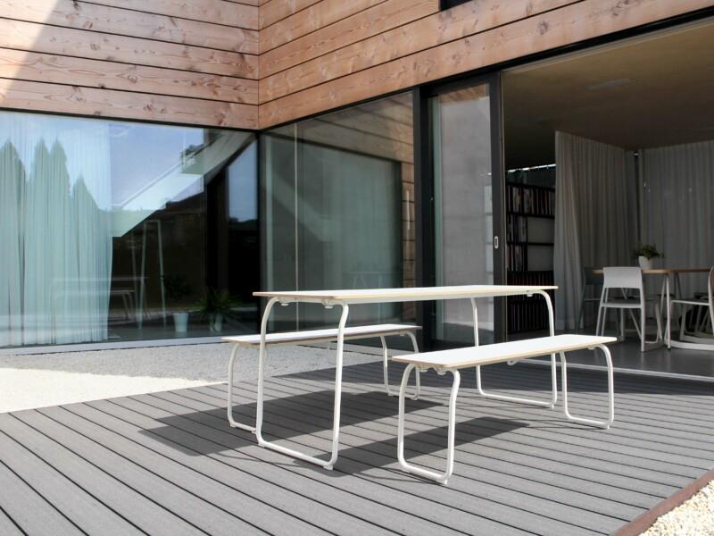 Dunkelgraue, wetterfeste Terrassendielen, weiße Sitzbänke und moderne Fassade
