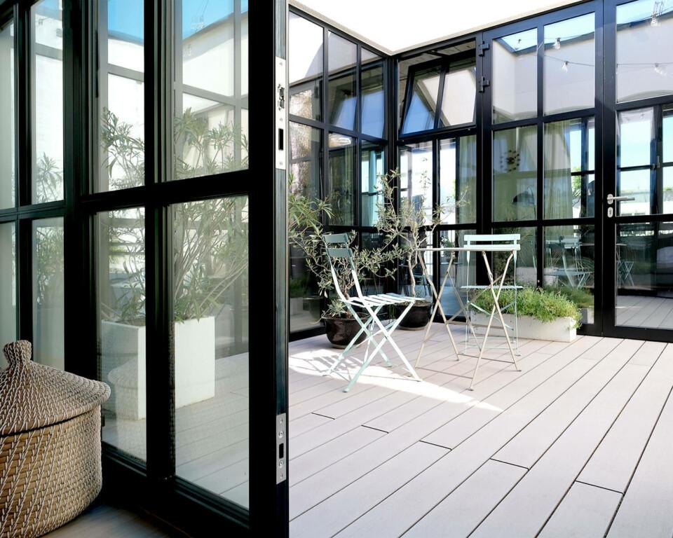 Terrasse mit glatten, hellgrauen WPC Dielen und moderner Terrassengestaltung