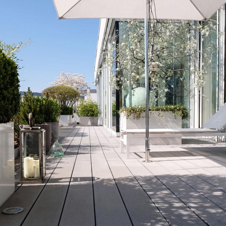 Moderne Terrasse mit WPC Dielen in grau, viel Balkonpflanzen, sowie moderner Liege