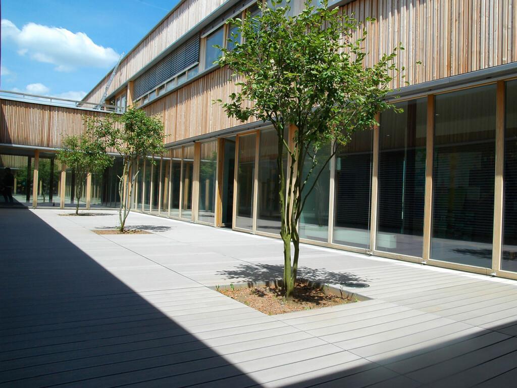 Die grauen WPC Dielen in dem Innenhof der Schule sind splitterfrei und ergänzen ideal die moderne Architektur.