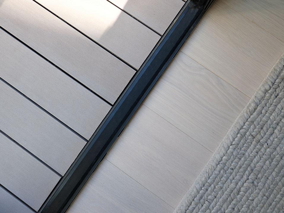 Übergang WPC Terrassendielen auf der Terrasse und Holzparkett im Innenbereich; in einer Richtung verlegt