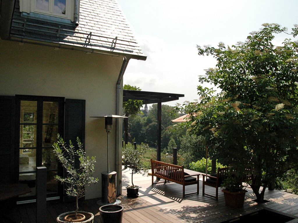 Die um das Haus herum verlegte Terrasse verläuft immer quer zur Hauswand