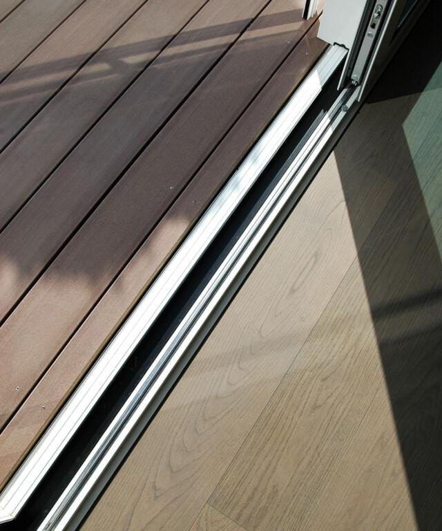 Die WPC Terrassendielen in dunklem braun sind wie das Parkett längs zu den Fenstern verlegt