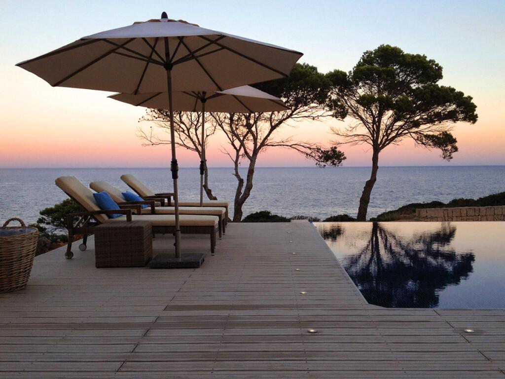 Poolumrandung aus WPC (Holz Kunststoff Dielen) bei Sonnenuntergang mit Blick aufs Meer