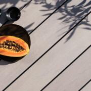 Graue WPC Terrassendielen mit glattem Design auf Terrasse mit Schatten von Baum.