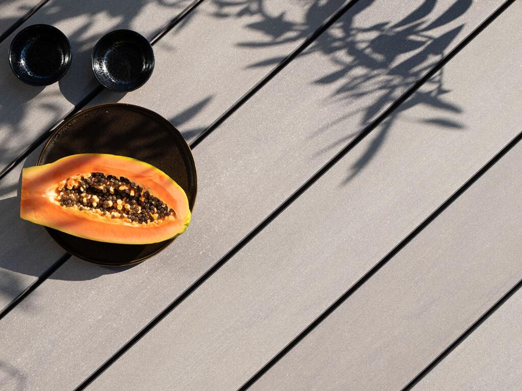 Größe für Mobile Version: Graue WPC Terrassendielen mit glattem Design auf Terrasse mit Schatten von Baum.