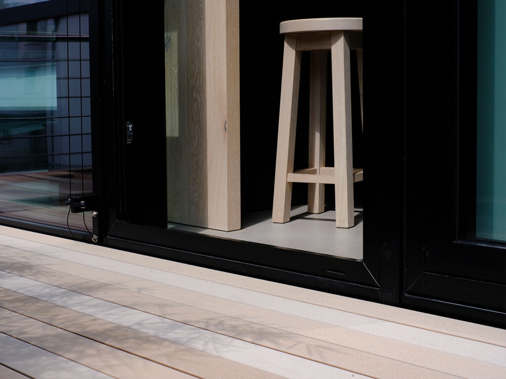Hellbraunes WPC vollprofil auf Terrasse mit Glasfassade und modernen Eichenmöbeln in hell innen