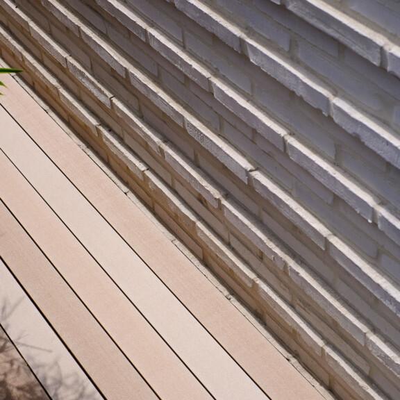 MYDECK WPC Massivdielen in hellen Brauntönen auf Terrasse mit angrenzendem Backsteingebäude