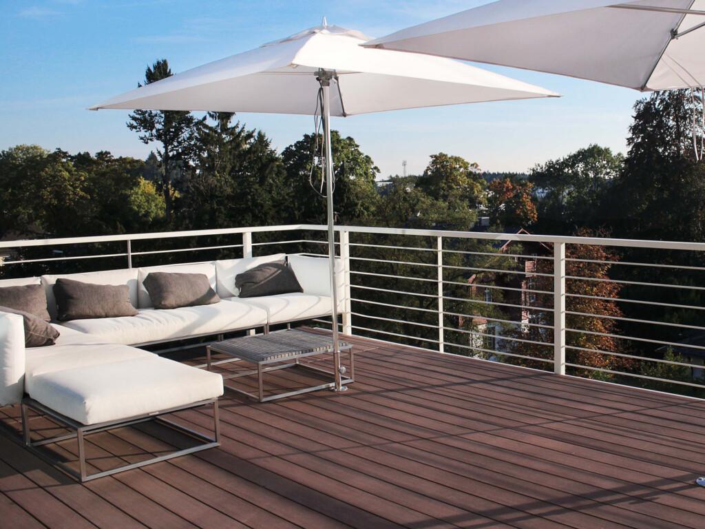 Langlebige dunkelbraune Terrassendielen auf einer Terrasse mit Outdoorsofa und aufgespannten hellen Sonnenschirmen