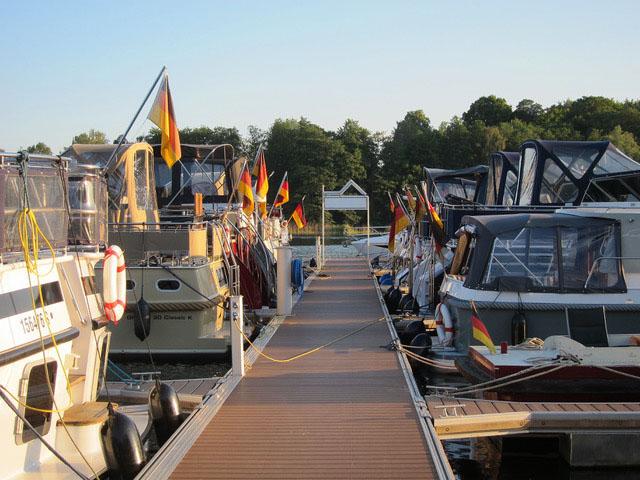 Braune WPC Dielen nach 12 Jahren Nutzung auf Bootssteg mit anlegenden Booten