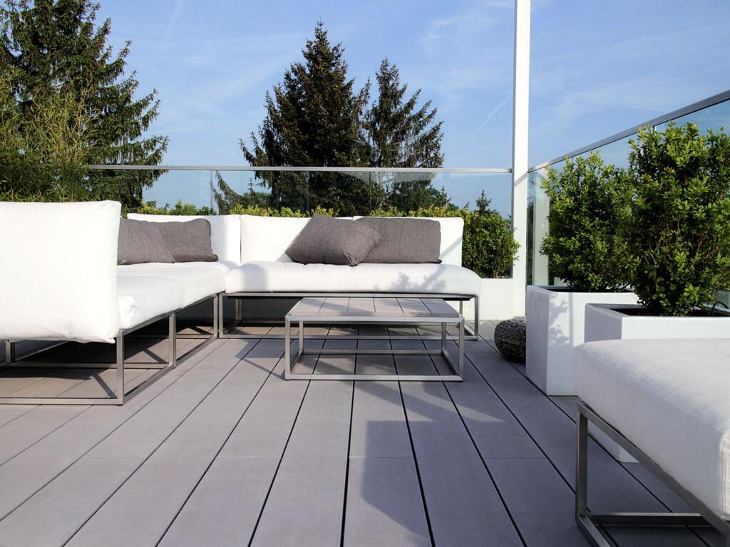 Graue WPC Dielen auf schraubenfrei verlegtem Balkon und modernen Möbeln
