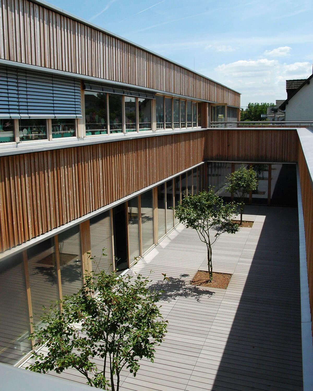 Innenhof mit grauen WPC Terrassendielen von MYDECK und Bäumen im Innenhof