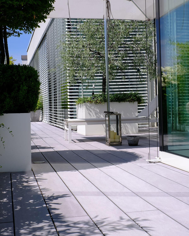 Moderne Terrasse mit grauen WPC Vollprofildielen - Terrasse mit integriertem Garten