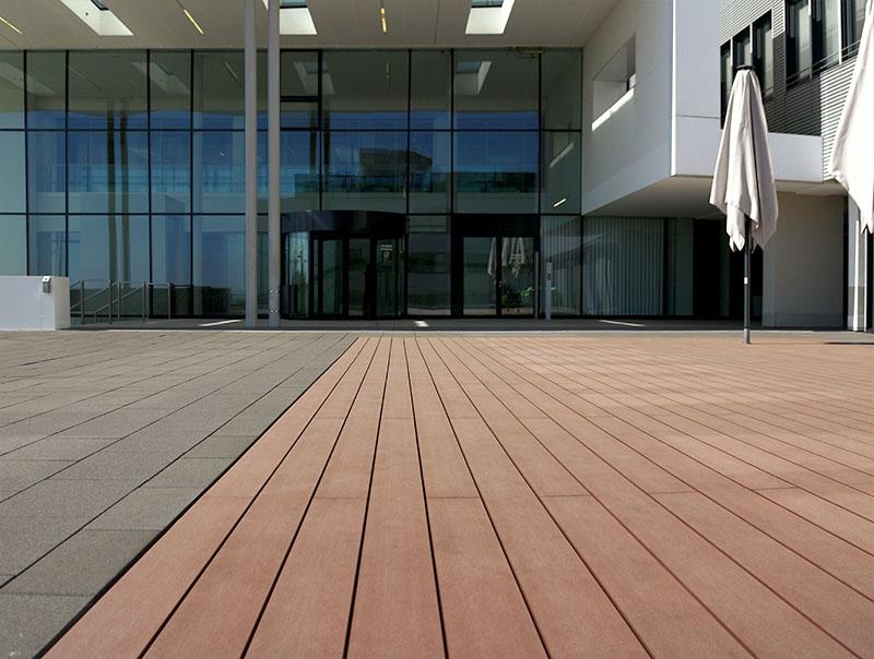 Terrassenbelag WPC Dielen glatt braun vor modernem Gebäude